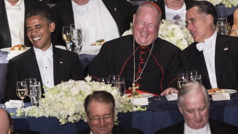 """Obama, Cardinal Timothy Dolan, and Republican presidential opponent Mitt Romney during the annual Al Smith Dinner in New York on October 18, 2012, in New York. Obama poked fun at Romney and himself, saying he was """"well-rested"""" from a """"long nap"""" during the pair's first debate."""