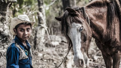 A boy and his blind pony in the countryside near Chimaltenango, Guatemala, February 2013. The boy's father was the local rag and bone man and with the boy riding the pony, they helped to pull his cart
