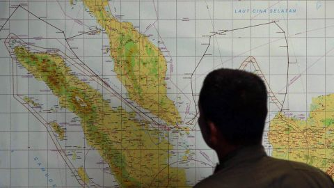 A member of the Indonesian Air Force at Medan city military base inspects the Indonesian military search operation for the missing Malaysian Airlines flight MH370 on March 12, 2014 in the area of Malacca Strait, a sea passageway between Indonesia (seen left of the map) and Malaysia (seen top left of the map). Malaysia faced a storm of criticism on March 12 over contradictions and information gaps in the hunt for a missing airliner with 239 people on board, as the search zone dramatically veered far from the intended flight path.       AFP PHOTO / ATAR        (Photo credit should read ATAR/AFP/Getty Images)