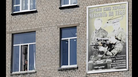 """A Ukrainian soldier looks out of the window of a regional military building with a poster reading """"Ukraine's armed forces wait for you!"""" in Donetsk on March 13."""