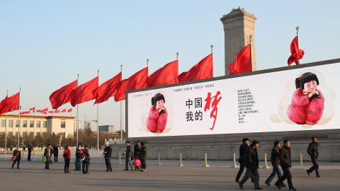 """In Beijing, citizens walk by a large banner reading """"Chinese dream."""""""
