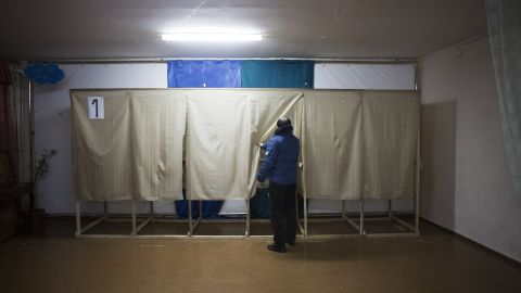 A member of a pro-Russian self-defense unit checks a polling station near Simferopol on March 13.