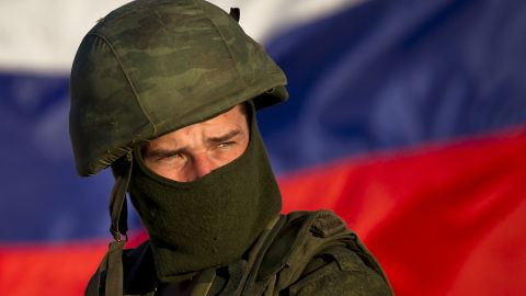A pro-Russian soldier, with the Russian flag behind him, mans a machine gun outside an Ukrainian military base in Perevalne on Saturday, March 15.