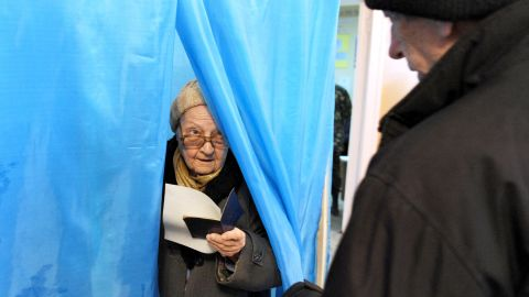 An eldery woman holds her ballot as she leaves a voting booth in one of the polling stations in Sevastopol on March 16, 2014. People in Crimea took to the polls on March 16 for a referendum on breaking away from Ukraine to join Russia that has precipitated a Cold War-style security crisis on Europe's eastern frontier. AFP PHOTO/ VIKTOR DRACHEV        (Photo credit should read VIKTOR DRACHEV/AFP/Getty Images)