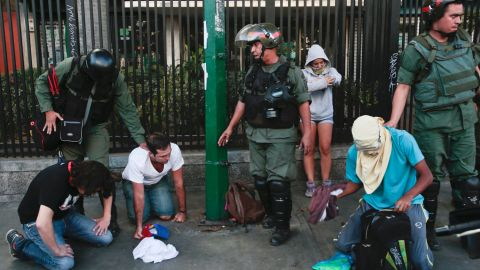 Anti-government protesters kneel as National Guardsmen arrest them in Caracas on March 16.