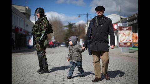 Civilians walk past riot police in Simferopol on March 17.