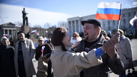 A man holds a RUSSIAN flag as he secures the Crimean parliament building in central Simferopol on March 17, 2014. Crimea declared independence today and applied to join Russia while the Kremlin braced for sanctions after the flashpoint peninsula voted to leave Ukraine in a ballot that has fanned the worst East-West tensions since the Cold War. AFP PHOTO / DIMITAR DILKOFF (Photo credit should read DIMITAR DILKOFF/AFP/Getty Images)