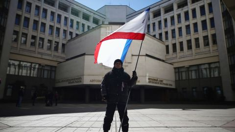 A man holds a Crimean flag in front of the Crimean parliament building on March 17, 2014 in Simferopol, Ukraine. People in Crimea overwhelmingly voted to secede from Ukraine during a referendum vote on March 16 and the Crimean Parliament has declared Independence and formally asked Russia to annex them