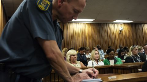 Steenkamp's mother, wearing the white collared shirt, looks on while a police officer takes notes in court March 18.