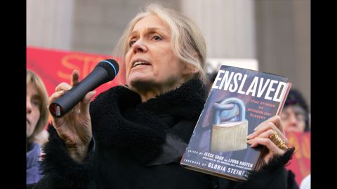 """Steinem holds up a copy of her book """"Enslaved"""" as she speaks during a 2007 protest on the steps of the state Supreme Court in Albany, New York."""