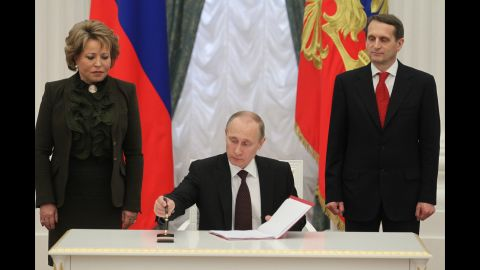 Russian President Vladimir Putin signs the final decree completing the annexation of Crimea on Friday, March 21, as Upper House Speaker Valentina Matviyenko, left, and State Duma Speaker Sergei Naryshkin watch.