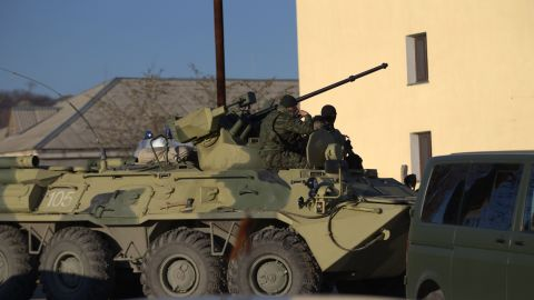 Soldiers in unmarked uniforms sit atop an armored personnel carrier at the gate of the Belbek air base on March 22.