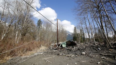 Downed power lines and parts of a destroyed house can be seen in the debris blocking the road near Oso on March 23.