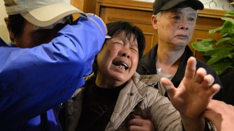 Relatives of passengers on Malaysia Airlines flight MH370 cry after hearing the news that the plane plunged into Indian Ocean at a hotel in Beijing on March 24, 2014.
