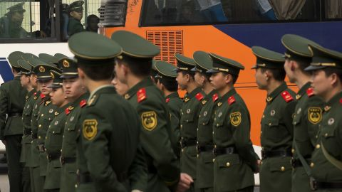 """A bus carrying paramilitary policemen drives past a team of paramilitary policemen blocking a road outside the Malaysian Embassy, where relatives of Chinese passengers on board the missing Malaysia Airlines Flight 370 are holding a protest, in Beijing, China, Tuesday, March 25, 2014. Furious over Malaysia's handling of the lost jetliner a day after the country said the passengers must be dead, Chinese relatives of the missing marched Tuesday to the Malaysia Embassy, where they threw plastic water bottles, tried to rush the gate and chanted, """"Liars!"""" (AP Photo/Alexander F. Yuan)"""