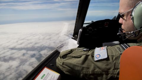 Flight Lieutenant Jayson Nichols looks out of the cockpit of a Royal Australian Air Force AP-3C Orion aircraft over cloud while searching for the missing Malaysian Airlines flight MH370 over the southern Indian Ocean on March 27, 2014.  Thunderstorms and gale-force winds grounded the international air search for wreckage from Flight MH370, frustrating the effort yet again as Thailand reported a satellite sighting of hundreds of floating objects.    AFP PHOTO / POOL        (Photo credit should read Michael Martina/AFP/Getty Images)