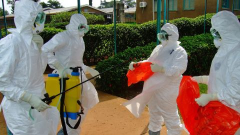 A picture taken on July 28, 2012 shows officials from the World Health Organization wearing protective gear as they prepare to enter Kagadi Hospital in Uganda's western Kibale district, around 200 kilometres (125 miles) from Kampala.