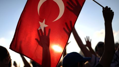A protester holds up a Turkish flag as others raise their hands during a demonstration in Taksim square in Istanbul on June 8, 2013. Thousands of angry Turks took to the streets on June 8 to join mass anti-government protests, defying Prime Minister Recep Tayyip Erdogan's call to end the worst civil unrest of his decade-long rule. Erdogan, meanwhile, was meeting in Istanbul with top officials of his Justice and Development Party (AKP) to discuss the crisis, and a deputy prime minister was due to make a speech later on June 8. AFP PHOTO/BULENT KILIC (Photo credit should read BULENT KILIC/AFP/Getty Images)
