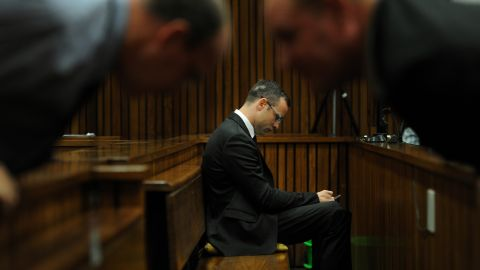 Pistorius sits inside the courtroom as members of his defense team talk in the foreground Friday, March 28.
