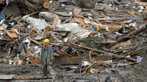 A searcher walks near a massive pile of debris in Oso on March 27.