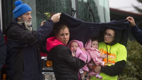 Ralph Jones helps provide shelter for Brooke Odenius, right, Klarissa Calviste and their baby daughters during the moment of silence at the fire house in Darrington.