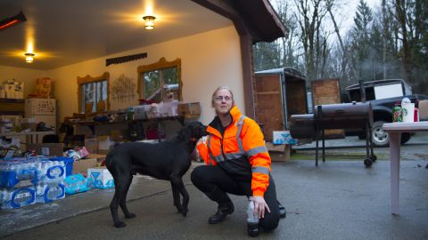 Elaine Young of Oso, Washington, pets her dog at a home used as a staging area for donated food and supplies.