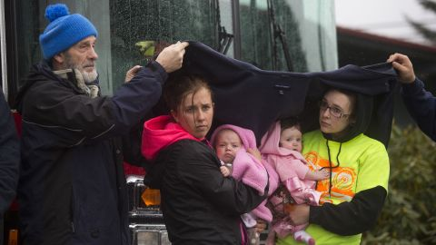 Ralph Jones helps provide shelter for Brooke Odenius, right, Klarissa Calviste and their baby daughters during a moment of silence Saturday at the fire house in Darrington.