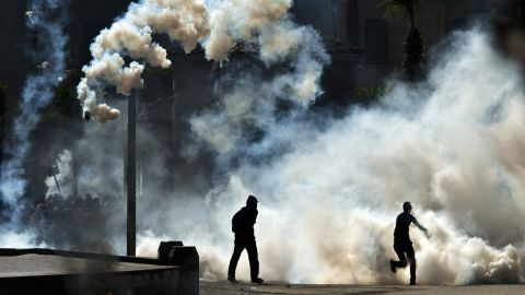 Egyptian students who support the Muslim Brotherhood and ousted Islamist president Mohamed Morsi run from tear gas fired by riot police during clashes following a demonstration outside Cairo University on March 26, 2014.