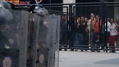 People shout insults at police Tuesday, April 1, during clashes between police and anti-government protesters in Caracas.