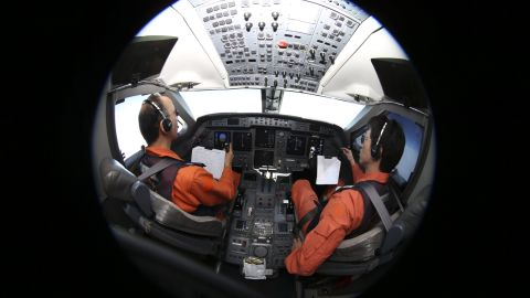 Captain of the Japan Coast Guard Gulfstream Makato Hoshi (L) and his co-pilot Shunichi Yumiza sit in the cockpit during the search for missing Malaysia Airlines flight MH370 over the southern Indian Ocean on April 1, 2014