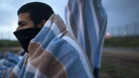 A Syrian refugee watches the sunrise Wednesday, April 2, after sleeping outside the Center for Temporary Stay of Immigrants in Melilla, Spain.
