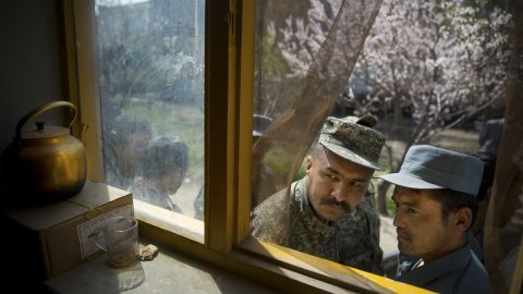 An Afghan soldier, left, and a policeman peek through a window of a school in Kabul, Afghanistan, as they line up with others to get their voter registration card on Tuesday, April 1.