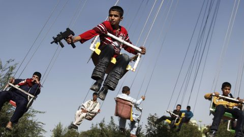 An Afghan boy holds a toy gun as he rides a merry-go-round in Kabul in September 2009.