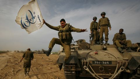 An Israeli soldier jumps off an armored vehicle carrying a flag of Israel's 60th anniversary as he celebrates with his unit in January 2009.