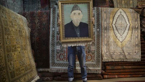 An Afghan carpet seller holds up a framed carpet depicting Afghan President Hamid Karzai on Sunday, March 30.