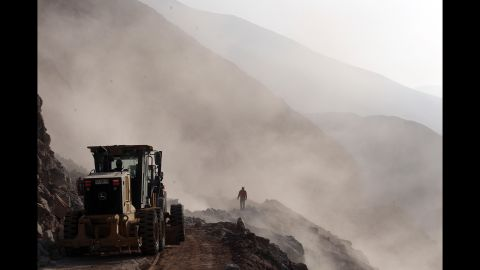 Heavy machinery is used to clear debris on the road leading to the town of Camarones, Chile, on Thursday April 3, after access to the town was cut off during an 8.2-magnitude earthquake that struck on April 1.