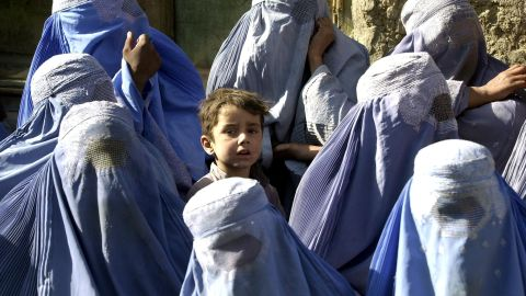 """A young boy stands among a group of veiled women waiting to receive food aid during a U.N. World Food Program distribution in Kabul in November 2001. """"I myself remember the mujahideen's takeover of Kabul on 27 April 1992,"""" says Mosadiq. """"On 26 April I wore a miniskirt and a sleeveless shirt, but the day after I was terrified to walk outside without being fully covered."""""""