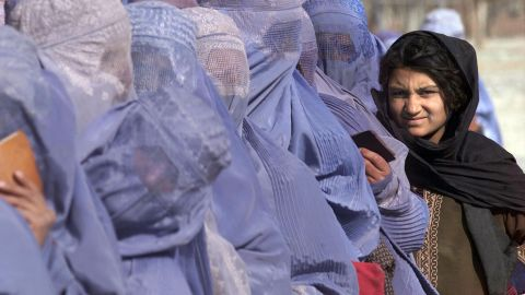 """Women wait to receive food aid during a U.N. World Food Program scheme in Kabul in December 2001. """"Even inside Afghanistan, female dress code varies hugely between regions,"""" says Mosadiq. """"You'll find the blue burqas across the whole country, but in urban centers like Kabul many women will only wear a hijab. In the north a white burqa is common, and in some Pashtun areas you'll find women in colorful dresses and just a headscarf."""""""
