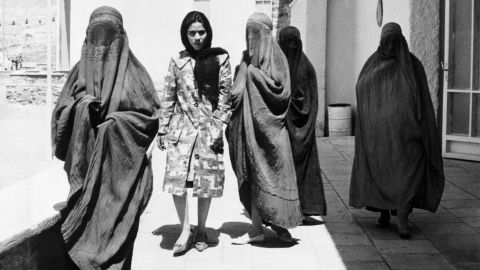 """Taken in 1962, this picture shows Afghan women walking along a street in Kabul. Four of them are wearing burqas, whereas one walks comfortably among them in European-style dress. """"When the mujahideen-led government replaced the Soviets in 1992, new restrictions on dress were formalized,"""" says Mosadiq, """"and obviously the Taliban's takeover in 1994 was the final nail in the coffin for any kind of independent dress for both men and women."""""""