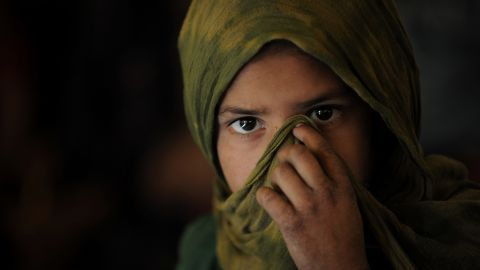 An Afghan Kuchi (Pashtun nomad) girl covers her face as she attends a class on October 27, 2010. She is being taught in a tent near the ruins of the Darul Aman Palace on the outskirts of Kabul.