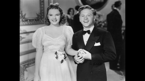 """Rooney hold hands with Garland in a 1940 still from the film """"Andy Hardy Meets Debutante."""""""