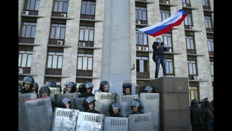 """Protesters wave a Russian flag as they storm the regional administration building in Donetsk on Sunday, April 6. Protesters seized state buildings in several east Ukrainian cities, prompting accusations from Kiev that Moscow is trying to """"dismember"""" the country."""