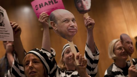 """Today, the top 1% controls about 40% of national wealth. At a hearing in Washington D.C. about Wall Street and the financial crisis, protesters hold a placard depicting Goldman Sachs CEO Lloyd Blankfein, who once famously said, """"I'm doing God's work.""""<br />"""