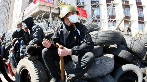 """A pro-Russian militant holding a bat guards a barricade in front of the Donetsk regional administration building on April 8, 2014. Ukraine mounted a counteroffensive on April 8 by vowing to treat the separatists as """"terrorists"""" and making 70 arrests in a nighttime security sweep, while hundreds of militants remained holed inside the Donetsk administration building a day after proclaiming the creation of an independent """"people's republic"""" and demanding that an independence referendum be held before May 11."""
