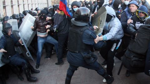 Pro-Russian supporters clash with members of the riot police as they storm the regional administration building in the eastern Ukrainian city of Donetsk on April 6, 2014.