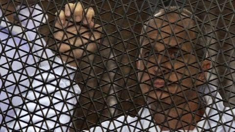 Australian journalist Peter Greste of Al-Jazeera looks on standing inside the defendants cage during his trial for allegedly supporting the Muslim Brotherhood at Cairo's Tora prison on March 5, 2014. The high-profile case that sparked a global outcry over muzzling of the press is seen as a test of the military-installed government's tolerance of independent media, with activists fearing a return to autocracy three years after the Arab Spring uprising that toppled Hosni Mubarak. AFP PHOTO / KHALED DESOUKI (Photo credit should read KHALED DESOUKI/AFP/Getty Images)