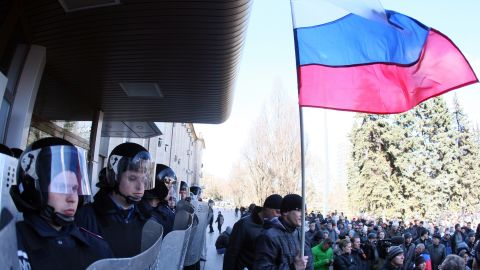 A man holds a Russian flag as police officers stand guard outside the regional government administration building in the center of the eastern Ukrainian city of Donetsk during a rally of pro-Russia supporters on April 5, 2014.