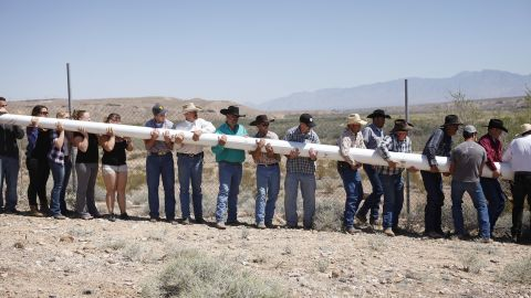 """People help erect a pole so that they could hang a banner April 7 in support of Bundy. One banner at the protest side stated: """"Has the West been won? Or has the fight just begun!"""""""