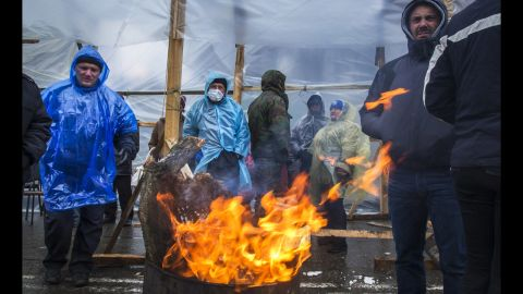 A group of pro-Russian activists warm themselves by a fire Friday, April 11, in front of a Ukrainian Security Service office in Luhansk.