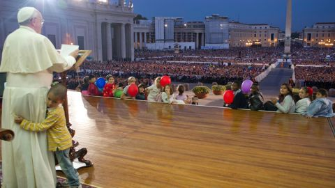 A young boy hugs Francis as he delivers a speech in St. Peter's Square in October 2013. The boy, part of a group of children sitting around the stage, played around the Pope as the Pope continued his speech and occasionally patted the boy's head.